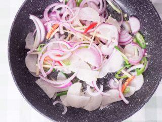 柠檬酸汤鲈鱼,平底锅里,油热后,依次放入蒜末、葱段、姜丝、酸萝卜、洋葱翻炒一会