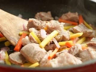 新疆特色手抓饭,加入胡萝卜条和羊肉,继续翻炒均匀