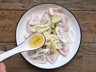 咸蛋黄鸡翅,将打好花刀的鸡翅放入容器中,加入葱姜蒜片,加适量的料酒。