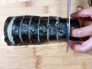 金枪鱼胚芽米寿司   便当,用刀将寿司卷切成均匀的小段儿。