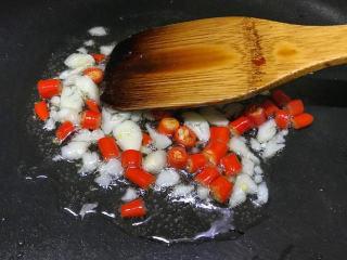 炒土豆丝,起锅烧火,锅热后倒入适量的食用油,先将蒜末与小米椒下入锅中小火爆香;