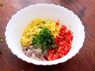 番茄虾仁鸡蛋水晶蒸饺,把炒熟的鸡蛋放入一个大一点的容器里,加入切碎的番茄和虾仁,再放入切碎的小葱。
