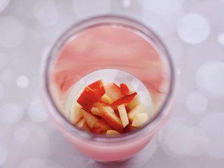 水蜜桃车厘子奶昔,把切小块的水蜜桃,放入料理杯。