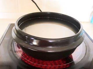宝宝爱吃的海鲜砂锅粥,把砂锅放在炉具上面,在砂锅里加入几滴玉米油,大火烧开后小火慢煲30分钟