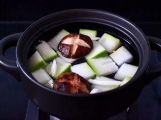 海浮鱼冬瓜冻豆腐煲,砂锅里倒入适量的清水,把冻豆腐和冬瓜,香菇放入锅中,倒入料酒。