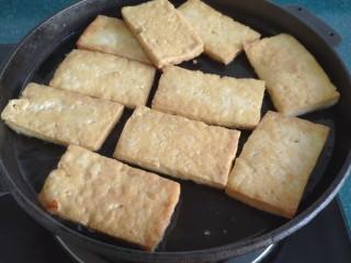 铁板豆腐,等到豆腐一面煎黄后,给它翻个儿面继续煎。