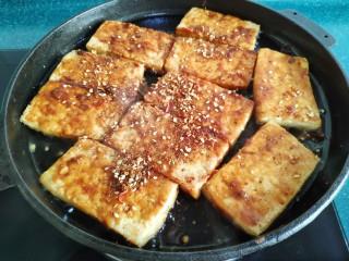铁板豆腐,两面都刷上酱料后,撒上调好的芝麻辣椒粉。