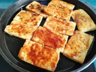 铁板豆腐,两面都煎好后,把火调到最小,刷上提前调好的酱料。