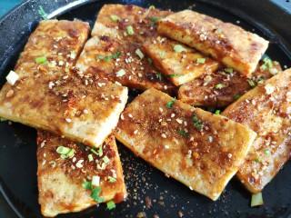 铁板豆腐,最后撒一把小葱香菜碎。
