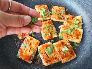 铁板豆腐,撒适量小葱圈,出锅前根据个人口味撒适量辣椒粉和孜然粉,白芝麻即可。