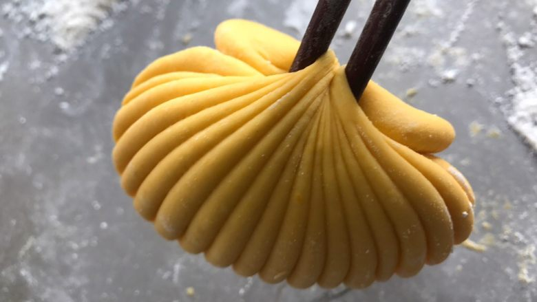 贝壳馒头,顺势提起来,然后将没有花纹的一面放在下面,将有花纹的一面覆盖在上面,稍微整理一下,一个贝壳就做好啦。