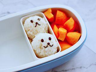 黄瓜双椒炒肉便当,把米饭做成饭团放入便当盒里,黄桃切成小块。