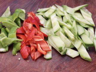 黄瓜双椒炒肉便当,把洗净的黄瓜,用刀切成菱形薄片,青红尖椒切片。