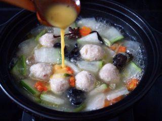 墨鱼丸子冬瓜木耳煲,倒入打散的鸡蛋液,继续大火烧开。