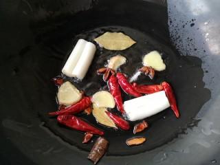 东北酱大骨,另取一锅加入适量油烧热下葱姜八角,干辣椒,香叶爆出香味。