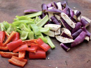 干煸烤肠茄条双椒,把茄子洗净后切成条,青红尖椒去籽后切成条。