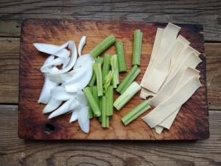 家庭版自制烤鱼,洋葱洗净切片,芹菜洗净切寸段,豆皮切条备用。