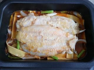 家庭版自制烤鱼,在配菜上放上煎好的鱼。
