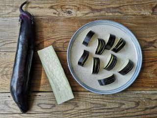 灯笼茄子,将长茄洗净,再竖着一切为二。用刀切分为六个为一小夹,五刀连一刀断,每片厚度大概2-3毫米。