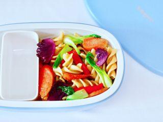 火腿肠时蔬炒意面便当,把炒好的意面放入便当盒里。