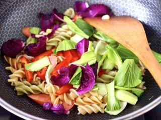 火腿肠时蔬炒意面便当,这个时候加入紫甘蓝和小油菜,再加入红椒条。