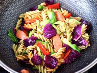 火腿肠时蔬炒意面便当,大火继续快速翻炒至所有食材,断生变色即可关火。