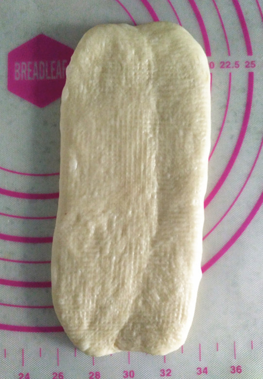 酸奶土司,取一个松弛好的面团,接口处朝上,从中间向两侧擀开后,再从一侧卷起。这一步不要卷的太紧,2.5圈左右为宜。