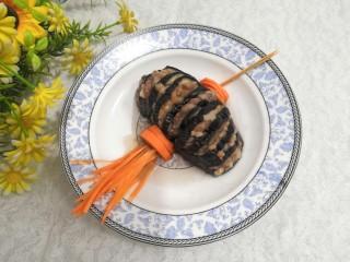 灯笼茄子,装盘后,点缀上胡萝卜,加上牙签,做成灯笼状,即可上桌
