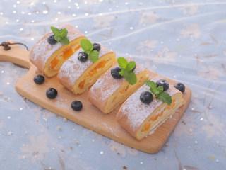 3款像云朵般柔软的瑞士卷,每一口都让人沦陷!,冷藏好后拿出来撒上糖霜,切成蛋糕卷,用蓝莓和薄荷装饰,芒果瑞士卷就做好啦,开吃吧~