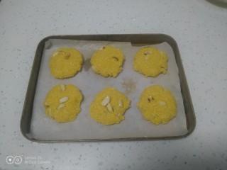 玉米面花生酥,平均分成40克一个,团成团再用手压扁,放入烤盘。