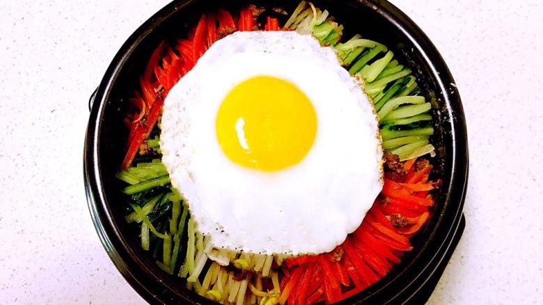 韩式石锅拌饭,再加入煎好的溏心蛋,把石锅放在燃气灶上加热,烧制锅内有滋滋的响声即可