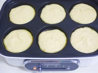 莲蓉馅南瓜椰蓉饼,放入多功能锅的模具中,底部撒少许椰蓉,先放一半面糊。