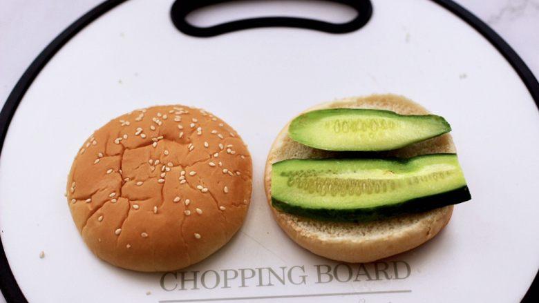 午餐肉黄瓜汉堡包,汉堡包胚上先放入一层切片的黄瓜。