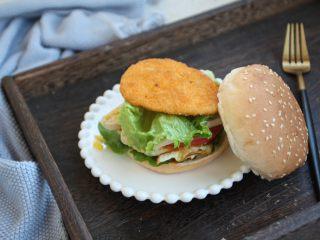 鸡肉玉米香肠汉堡,再放上1片生菜,放上煎好的黄金鸡饼。