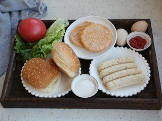 鸡肉玉米香肠汉堡,准备好食材:汉堡胚子、自制太阳谷鸡肉玉米香肠、黄金鸡肉饼、鸡蛋、番茄、生菜、番茄沙司、沙拉酱。食材可就地取材,喜欢吃什么就放什么。