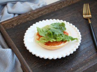 鸡肉玉米香肠汉堡,汉堡胚子抹上番茄沙司,放上生菜。