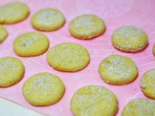 奶香南瓜芝麻饼,然后压扁,上面撒一层白芝麻。