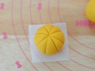 南瓜糕,用刀背在表面压出4条线,形成南瓜的纹路,之后将南瓜放到油纸上