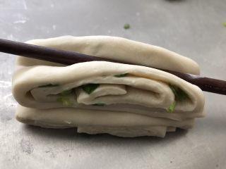葱油花卷,用筷子横向在中间压一下,端起来从中间轻轻往两边拉开一点。