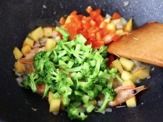 苹果北极虾时蔬炒饭,大火继续翻炒至所有的食材后,加入焯过水的西兰花和红椒丁,大火继续翻炒均匀。
