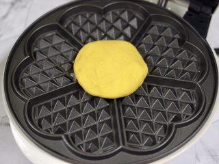 南瓜酸奶华夫饼,华夫饼机提前预热后,刷上薄薄的一层黄油,把摁扁的面饼放入机器里,盖上盖子开始烙制。