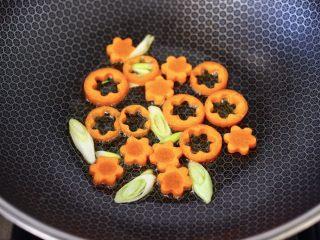 黄瓜墨鱼丸子汤面,锅烧热后,倒入花生油,小火把胡萝卜翻炒变软,再爆香葱花。