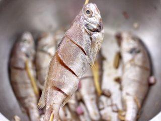 香辣孜然烤鱼,把腌制好的鱼,用竹签串起来。