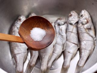 香辣孜然烤鱼,把改好花刀的鱼,放入盆中,加入适量的盐。
