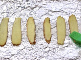香辣孜然烤鱼,烤盘上铺上锡纸,放入姜片,这是为了在烤鱼的时候,不让鱼皮脱落掉,软化后的黄油,用刷子蘸少许把姜片刷一层薄薄的黄油。
