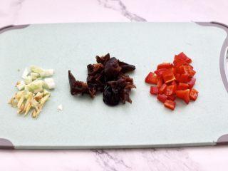 芸豆鱿鱼打卤面,泡发好的木耳用手撕成小块,葱姜切碎,红椒切成小丁。