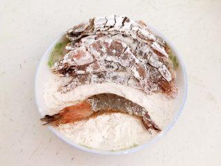 干锅基围虾,去一只腌制入味的基围虾放入面粉中打个滚,让基围虾均匀的裹上一层薄薄的面粉