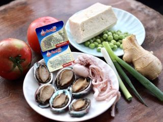 鲍鱼番茄海鲜豆腐浓汤,首先备齐所有的食材,冻豆腐提前拿出来解冻,桃花蛸和鲍鱼洗净。