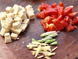 鲍鱼番茄海鲜豆腐浓汤,冻豆腐用刀切小块,番茄用刀也切成小块,葱姜切丝。