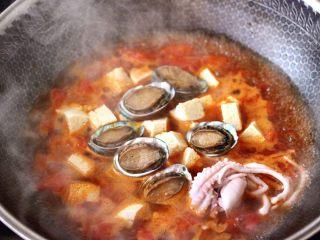 鲍鱼番茄海鲜豆腐浓汤,再放入鲍鱼和桃花蛸,大火煮沸后转中火继续煮10分钟。